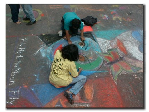 Picture of two children drawing with chalk on the street