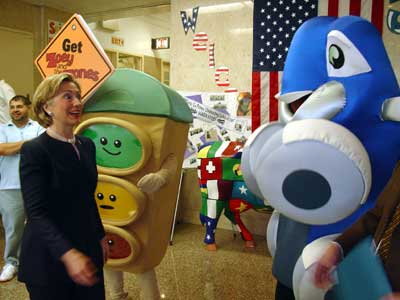 U.S. Senator Clinton at JHS 45 with two characters from Respironics, Zoey (the blue car) and Light Buddy (the traffic light).