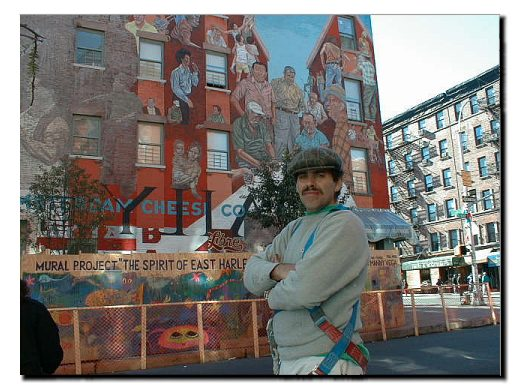 Color picture of community artist Manny Vega.  In the background stand the East 104th street wall mural which he has restored.