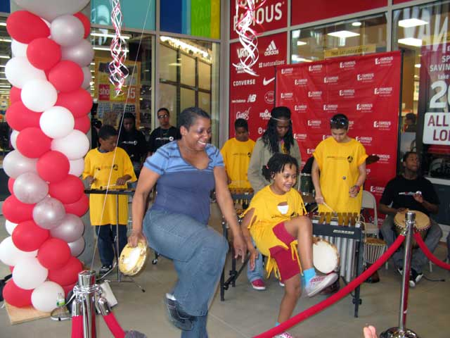DeVeor Rainey CEO/Founder Speaking in Rhythms Inc. dances with one of her students during a Famous Footwear store opening.