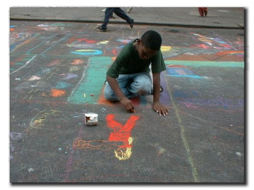 Picture of a little boy drawing with chalk on the street