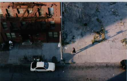 Photo of lone individual walking down a street.  Photo taken from the roof of 310 East 102nd Street in the early 90s